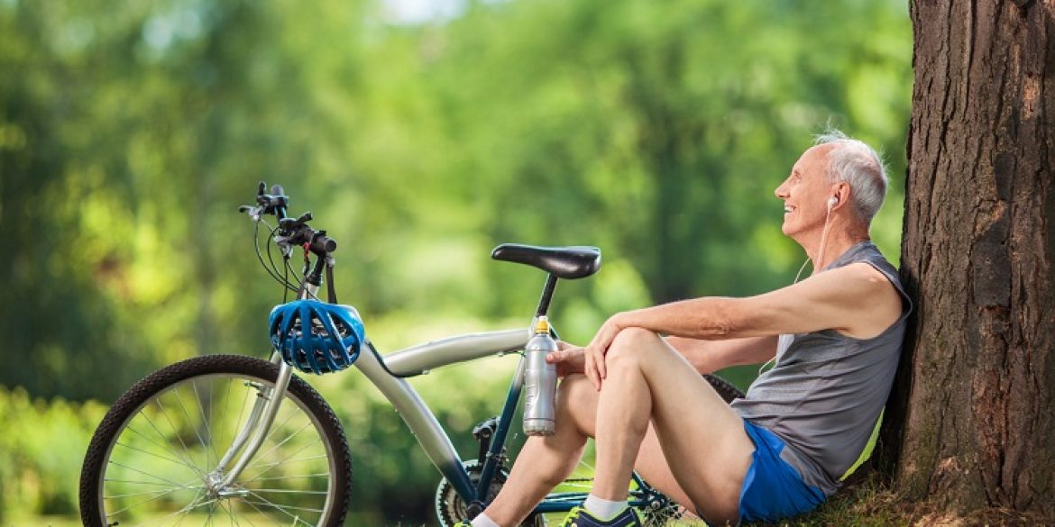 41856882 - active senior man listening to music on headphones seated by a tree in a park
